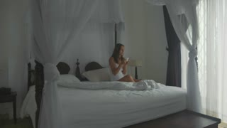 Young woman in underwear sits on the bed at bedroom, and rinks coffee.