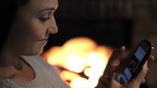 Young woman sitting in front of the fireplace with smart phone in her hands