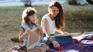 Young woman teaching drawing a girl at the park in sunny summer day.