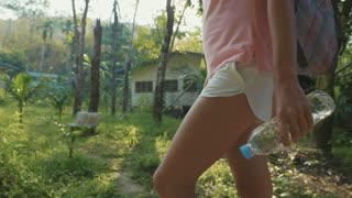 Young woman walking on countryside path through asian village, slow motion.