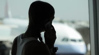 Young woman with smart phone at the airport with airplane on the background