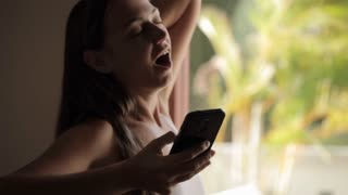 Young woman with smart phone yawning and stretching near the window.