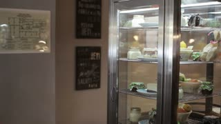 Waiter open the door of fridge and take a cake for customers