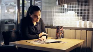 Woman looking at menu in restaurant and choosing plates