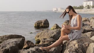 Yong woman making notes in diary on the beach