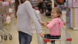 Young attractive mother with little girl buys decorate for Christmas-tree.