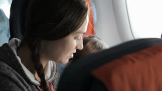 Young attractive woman with little daughter traveling at airplane.