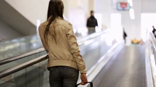 Young attractive woman with shopping basket riding escalator in shoping centre,