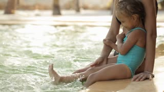 Young mother and little cute daughter sits and hugs on poolside at sunset
