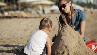 Young mother in dress and little daughter build castle with sand on the beach.