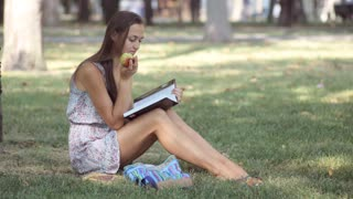 Young woman reading book and eating apple in park.