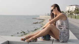 Young woman sitting and looking on the sea