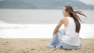 Young woman sitting on the beach with bad weather and looking on the sea.