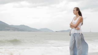 Young woman standing on the beach with bad weather and looking on the sea.