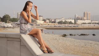 Young woman talk on mobile phone at seafront