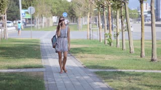 Young woman talking on mobile phone while walking in park.