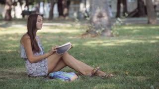 Young woman writes in her diary in the park