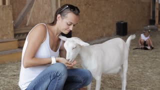 Young women feeding goat from hand