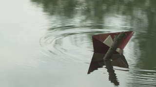 a paper boat in the river bends around the stick