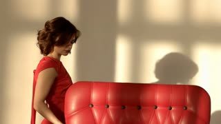 A young girl is sad and depressing. The woman touches the red armchair.