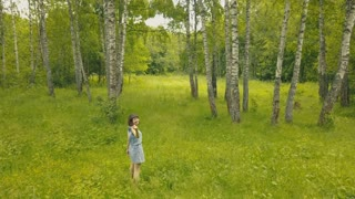 Arial view smiling young woman in forest. Follow me into forest