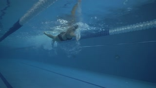 Female swimmer swims crawl stroke on swimming path in transparent water pool