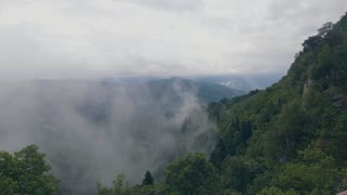 Foggy clouds in mountain valley and hills covered green forest. Misty haze in highlands