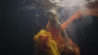 Mysterious woman swimming like mermaid under water in on dark background