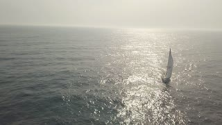 Sailing yacht with in blue sea and sunlight reflecting from water aerial view