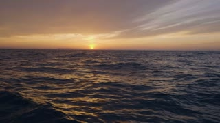 Scenic view from sailing ship on golden sunset in sky and sea waves
