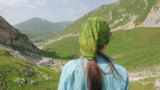 Tourist woman looking on green mountain valley landscape while summer hiking