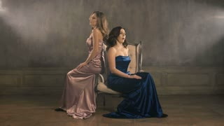 Two girls singer sit on a chair and sing. 4k longshot. Blue and pink evening luxurious dresses. Blond and Brunette woman.