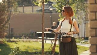 Woman walking beside riding bicycle on city park. Woman bike park