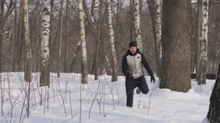 Young man running on snow drift in winter forest. Winter training outdoor