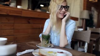 Beautiful Girl Talking on the Phone and Drinking Herbal Tea in a Cafe