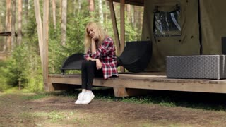 Beautiful Woman Sitting in a Large Tent in the Woods