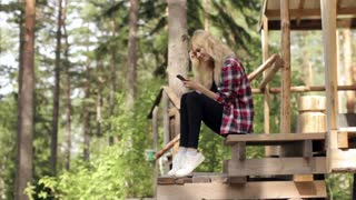 Beautiful Woman With Phone Sitting in a Large Tent in the Woods