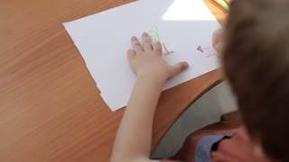 Boy Draws a Picture of House, Sitting at the Table