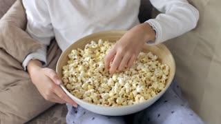 Boy Eating Popcorn on a Sofa