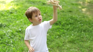 Boy Plays With Wooden Airplane on a Meadow