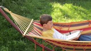 Boy Reads a Book While Lying in a Hammock
