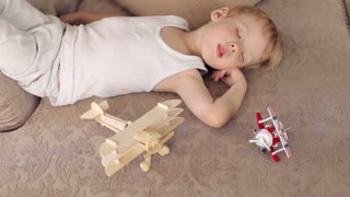 Boy Sleeping on a Sofa Among the Toys Plane