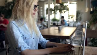 Business Woman Working at a Laptop in a Cafe