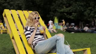 Girl Drinks Fruit Juice Sitting on a Lounger