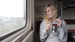 Girl Drinks Tea Sitting by the Window in a Train