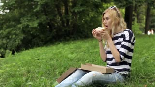 Girl Eating a Pizza Sitting on the Meadow