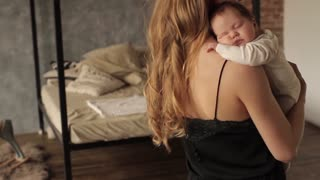 Girl in a Black Dress Holding a Baby in Her Arms