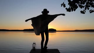 Girl in a Poncho and a Hat Fun, Dancing to the View of the Sunset on the Lake