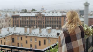Girl Sheltered Blanket With Tea on the Balcony Overlooking the City