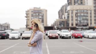 Girl Talking on the Phone While Standing on Street Parking on the Background of Houses